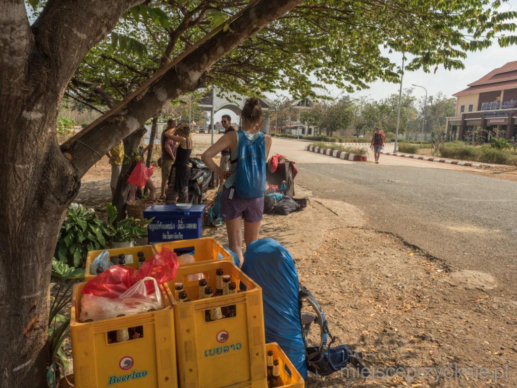 Czekamy na transport po przekroczeniu granicy, w krajobrazie dominują skrzynki z piwem Beerlao